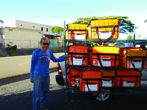 A Lanakila Meals on Wheels volunteer delivers food... and a smile.