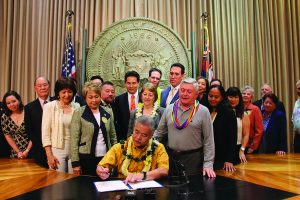 Gov. David Ige signs the Act into law at a ceremony with supporters.