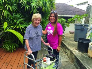 Photo of elderly woman being helped by of Hawaii Meals on Wheels