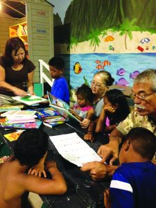 Volunteers encourage children by reading at the Next Step Shelter.