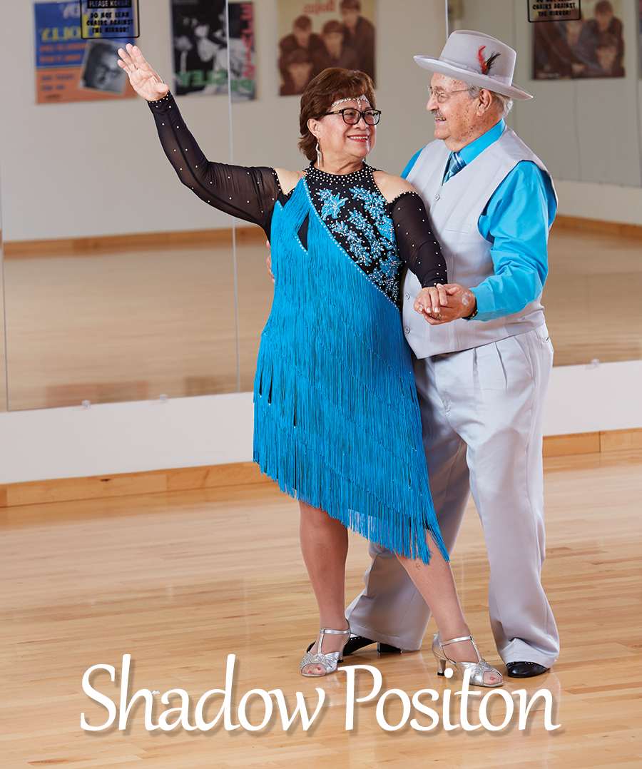 """Showmanship and Promotion -Love often urges us to put the spotlight on our partner; a common goal may require us to promote our partner's skills. Togetherness takes a different shape when we must lead from behind, or face the public on behalf of our partner in the wings. The """"Shadow Position"""" seen in many ballroom dances and in couples figure skating, represents this kind of relationship. The man dances behind the woman for several measures of music. The couple holds hands as a way of keeping balance and communicating. Senior Instructors David and Lea Twigg demonstrate the """"Shadow Position"""" as David shows off Lea and they both express a deep enjoyment of the dance and each other."""