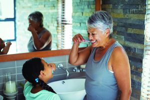 Grandmother and granddaughter brushing teeth in the bathroom at home